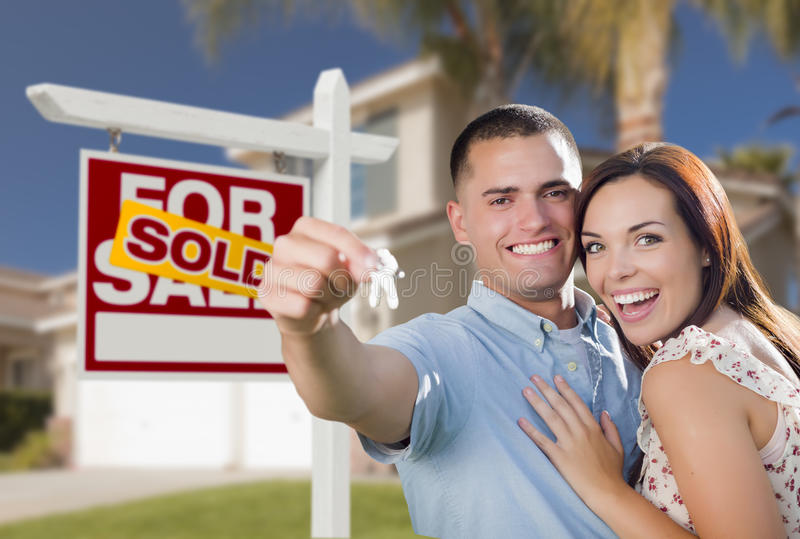 Military Couple In Front of Home, House Keys and Sign. Mixed Race Excited Military Couple In Front of New Home with New House Keys and Sold Real Estate Sign stock photography
