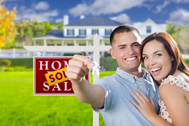 Military Couple In Front of Home, House Keys and Sign. Mixed Race Excited Military Couple In Front of New Home with New House Keys and Sold Real Estate Sign royalty free stock images