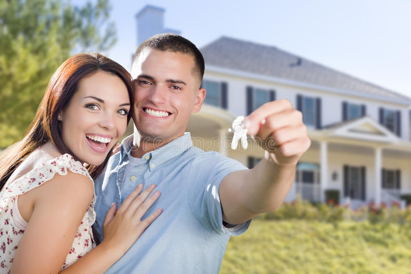 Military Couple with House Keys In Front of New Home. Mixed Race Excited Military Couple In Front of New Home Showing Off Their House Keys stock image