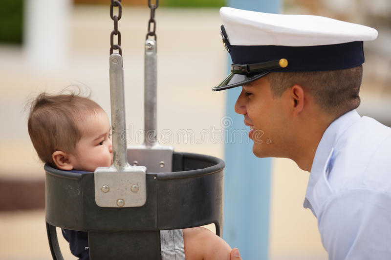 Military dad with his son. Stock image of a military dad swinging his son in the park royalty free stock photo