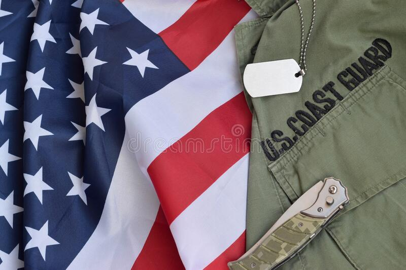 Military dog tag token and knife lies on Old US Coast Guard uniform and folded United States Flag. Background for Coast Guard day design royalty free stock image