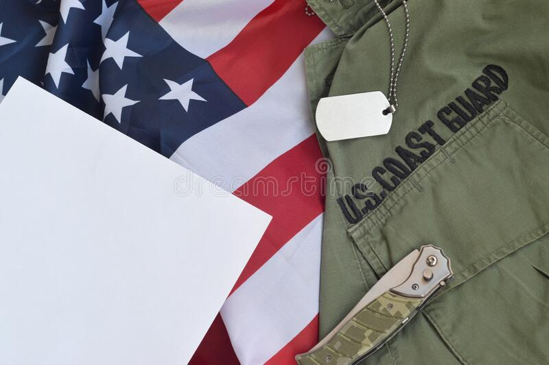 Military dog tag token and knife lies on Old US Coast Guard uniform and folded United States Flag. Background for Coast Guard day design stock images