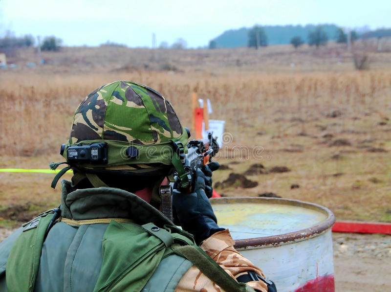 Military exercice. A soldier that aim after some terrorists that run and fire at them stock image