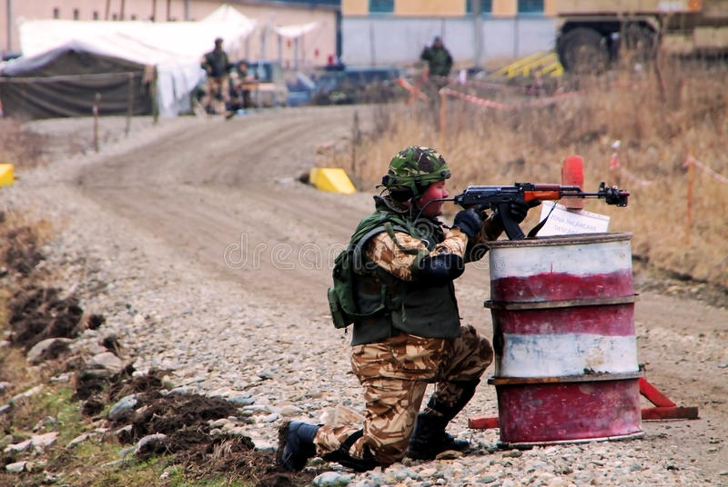 Military exercice. A soldier that aim after some terrorists that run and fire at them royalty free stock images