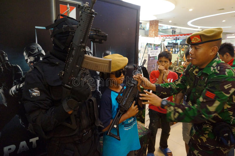 Military expo. Children and adolescents taking pictures with a firearm during the event at a mall Military expo city of Solo, Central Java, Indonesia royalty free stock photography