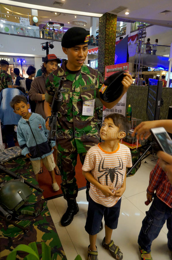 Military expo. Children and adolescents taking pictures with a firearm during the event at a mall Military expo city of Solo, Central Java, Indonesia stock images
