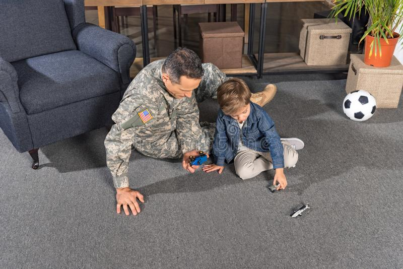 military father and son playing with toys while sitting on floor stock images
