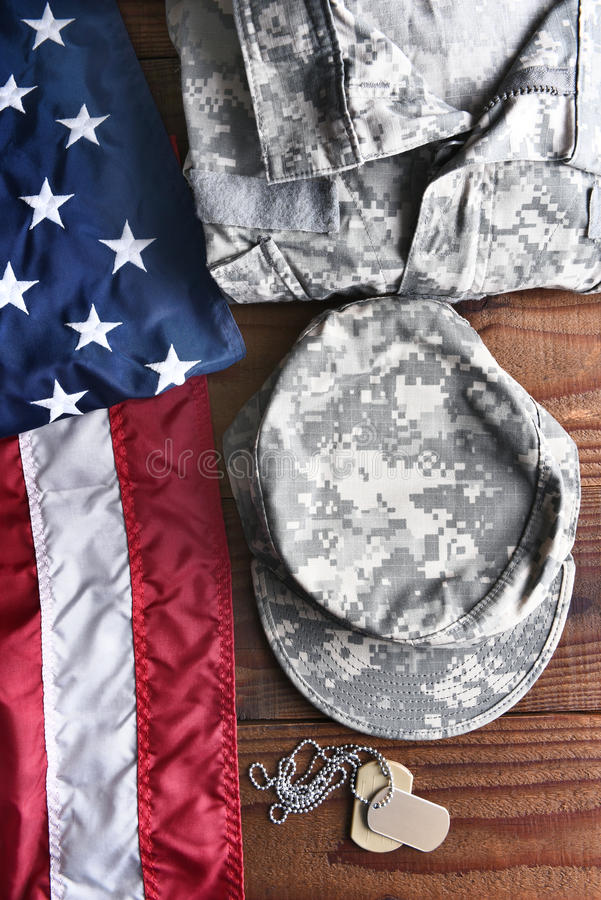 Military Fatigues Flag Dog Tags. Top view of military fatigues, dog tags and American Flag on a wood background. Military service concept for Memorial Day stock photography