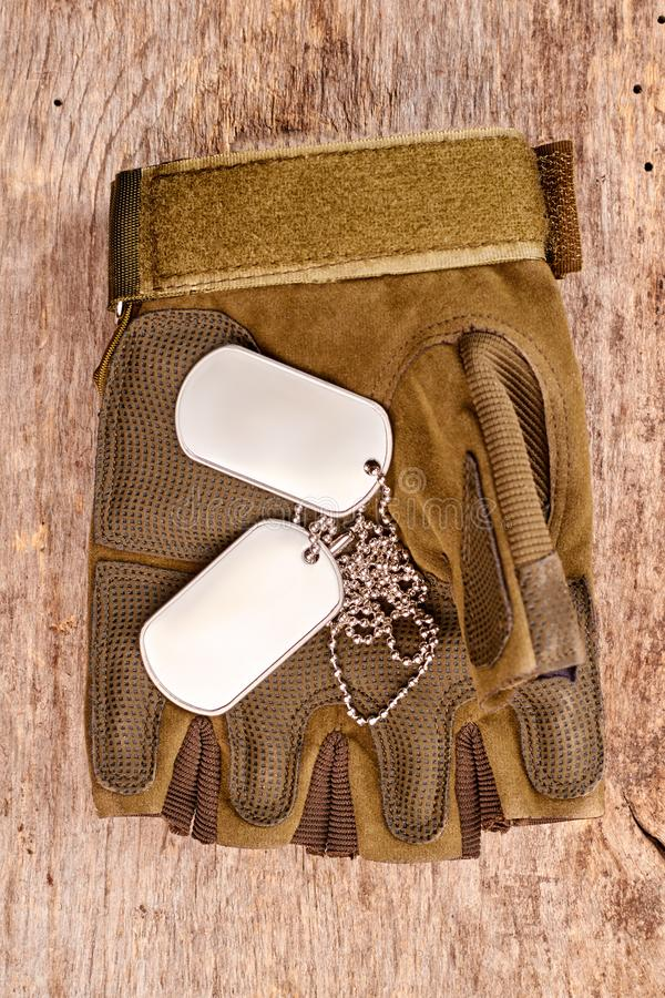 Military fingerless glove and dog tags. Close up, top view. Wooden desk surface background stock photo