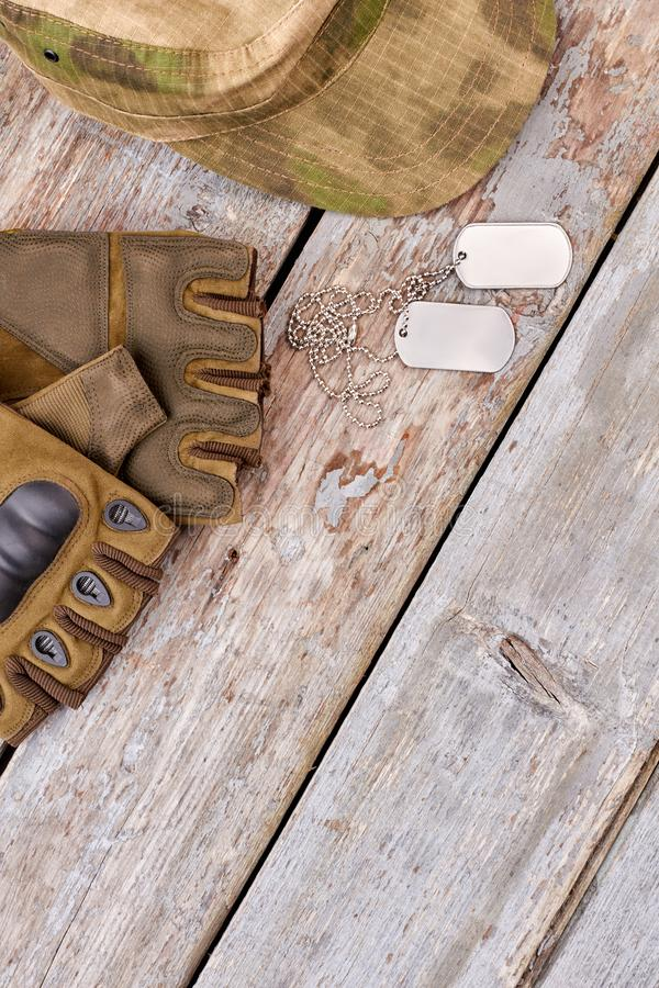 Military fingerless gloves, cap and dog tags. Top view, flat lay. Wooden desk background stock photos