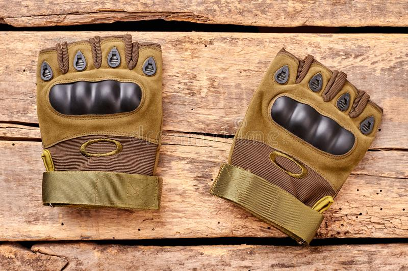 Military fingerless gloves on wood. Brown desk surface background stock image