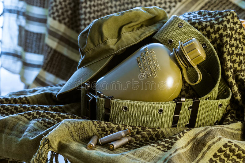 Military Flask, cap and ALICE belt lying on olive shemagh with a royalty free stock photo