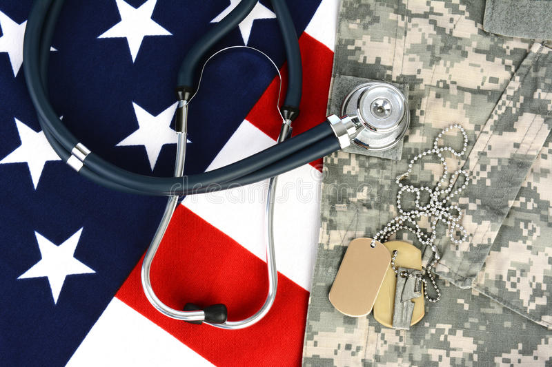 Military Health Care Concept. Military fatigues and dog tags on an American Flag with a stethoscope to illustrate health care in the armed services. Horizontal royalty free stock photos