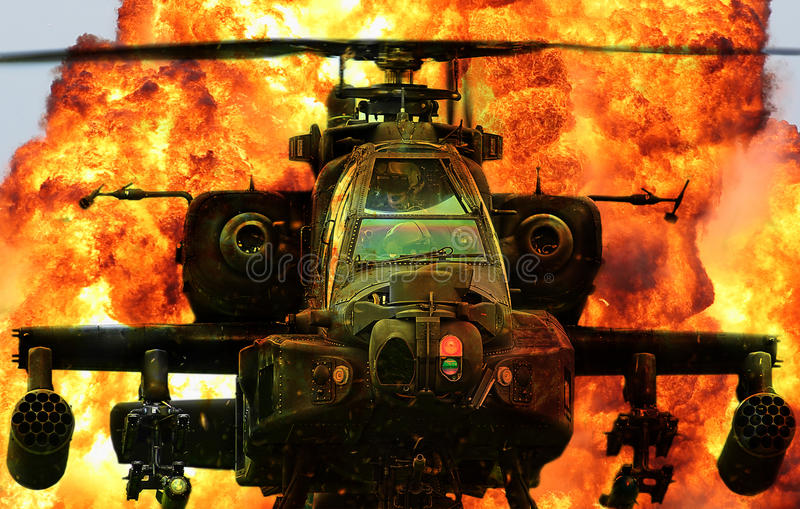 Military helicopter Apache explosion. Military Apache helicopter flying through explosion stock photography