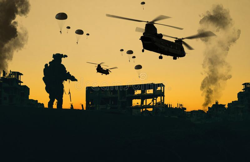 Military helicopter and forces in destroyed city in sunset royalty free stock images
