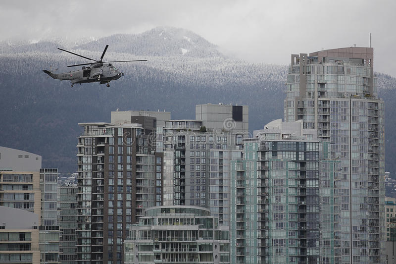 Military Helicopter Over City Skyline stock photos