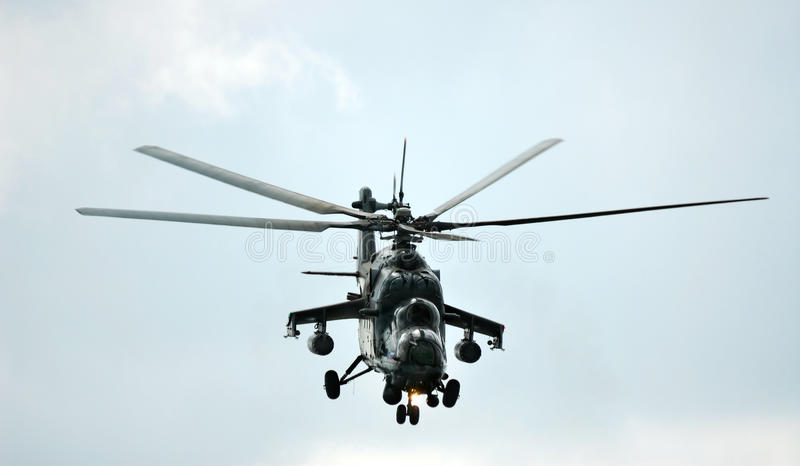 Military helicopter performing aerobatic elements stock photo