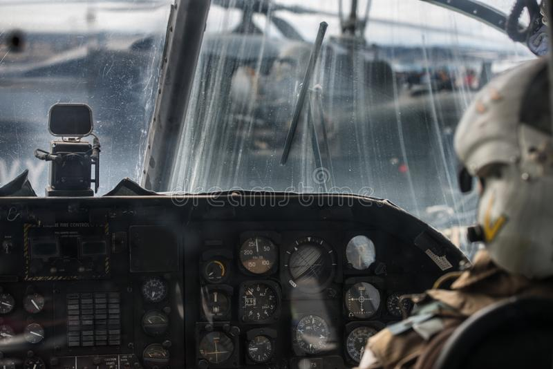 Military helicopter pilot operate in navy aircraft cabin at army base.  royalty free stock images