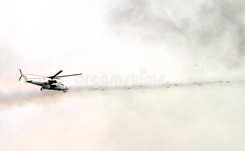Military helicopter shoots. Flying military helicopter shoots 1 royalty free stock images