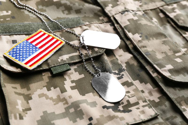 Military ID tags and US army flag patch on camouflage royalty free stock photography