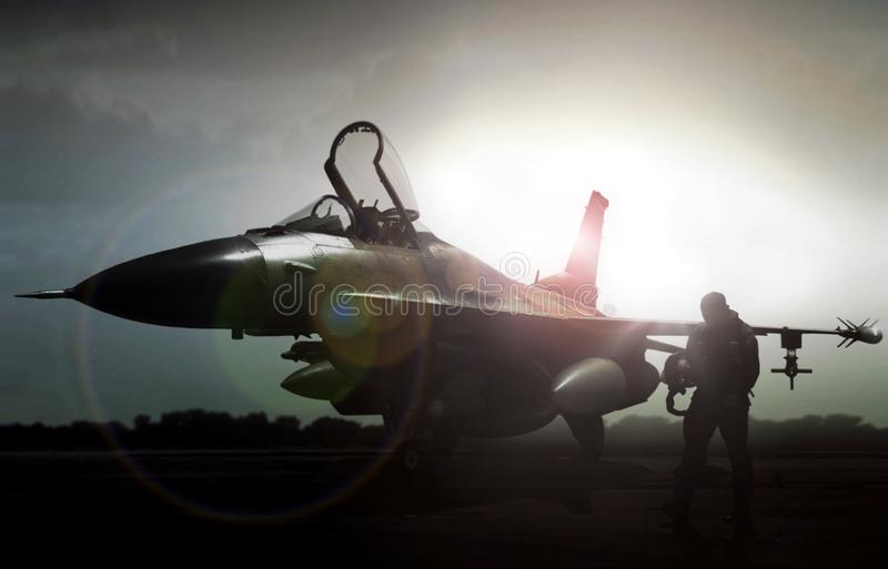 Military jet in silhouette with pilot walking away. Under bright morning lights stock photography