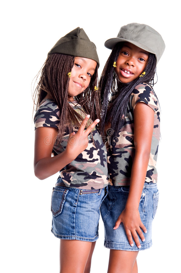 Military Kids For Peace. Two little African American girls dressed in denim skirts and military woodland camouflage tops and caps flashing peace signs stock photos