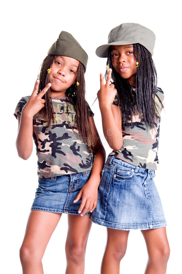 Military Kids For Peace. Two little African American girls dressed in denim skirts and military woodland camouflage tops and caps flashing peace signs royalty free stock photography