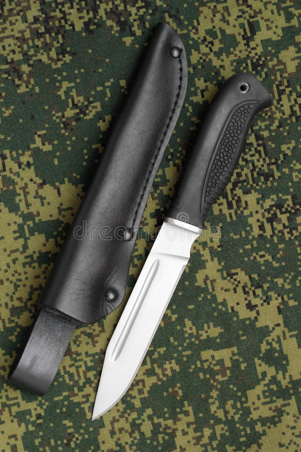 Military knife lying parallel with black leather sheath on camouflage background