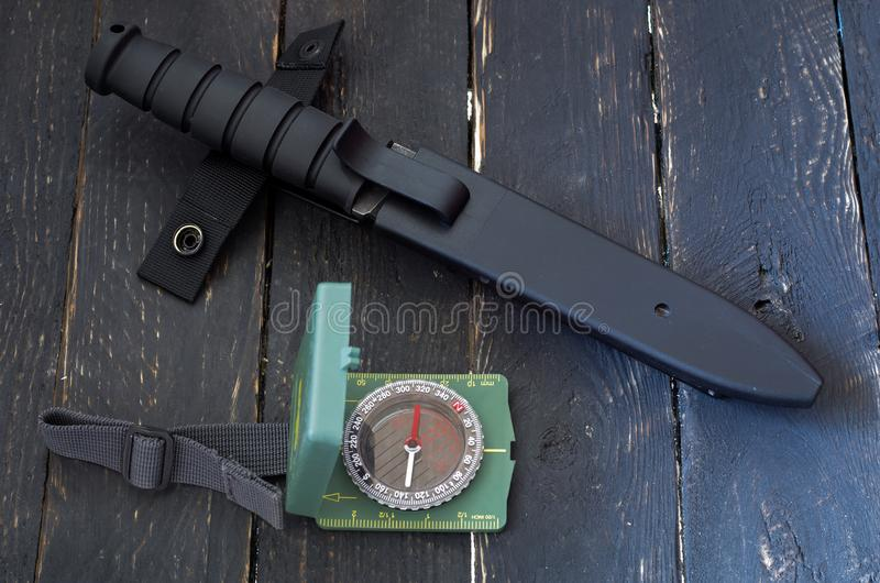 Military knife in plastic sheath. Compass for orientation. Top view. stock images
