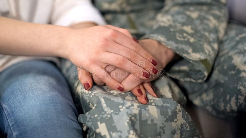 Military man and girlfriend holding hands, supporting boyfriend before leaving. Military men and girlfriend holding hands, supporting boyfriend before leaving royalty free stock image