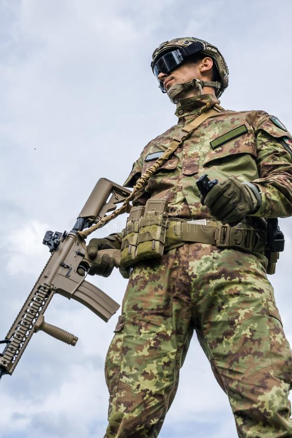 Military man holding automatic rifle and hand grenade royalty free stock image