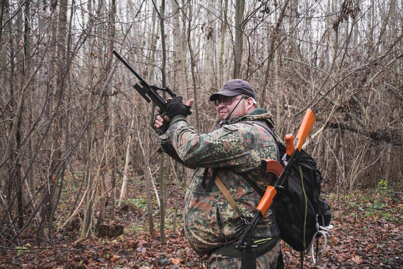 Military man with machine guns and camouflage in the forest. Military concept stock photography