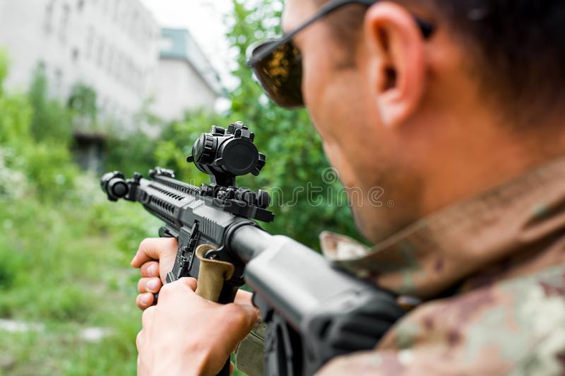 Military man with automatic rifle and rifle scope stock image