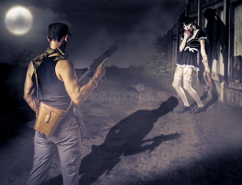Military man and female zombie. Military men with a gun looking at female zombie with a bloody ax royalty free stock image