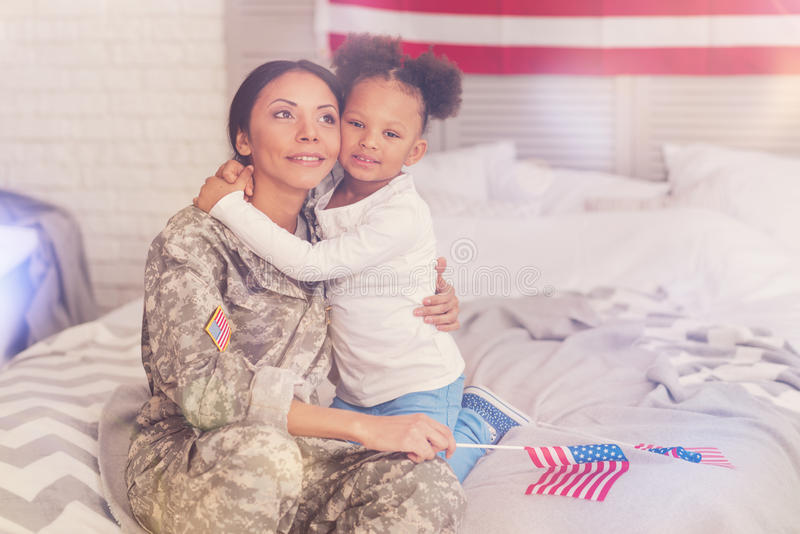 Military mother and daughter bonding to each other on bed royalty free stock photos