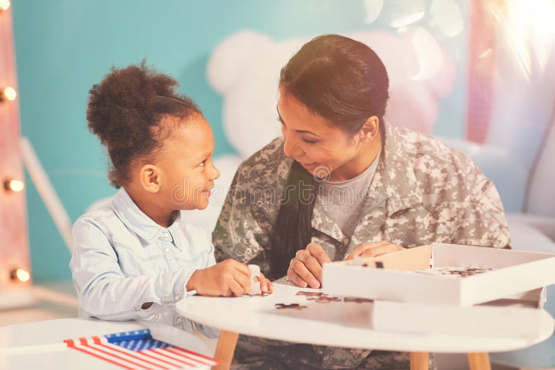 Military mother and her daughter doing a jigsaw puzzle stock photos