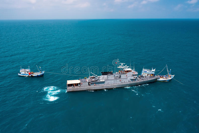 Military navy ships in a sea bay with fishing boat royalty free stock image