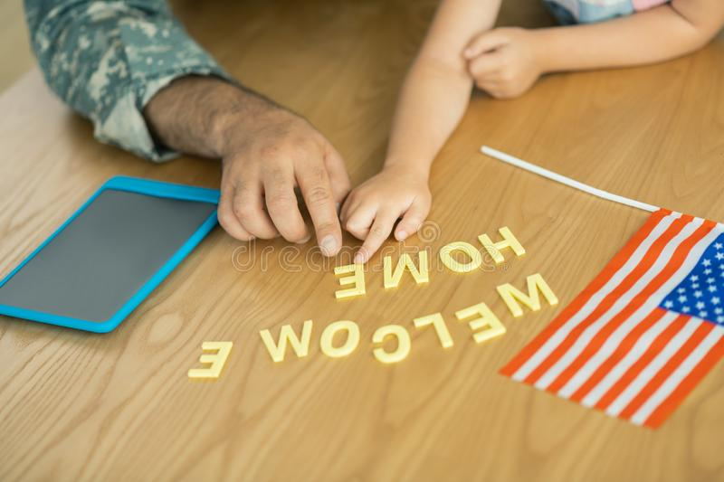 Military officer and daughter sitting at the table with flag and tablet. Flag and tablet. Close up of military officer and daughter sitting at the table with royalty free stock photo