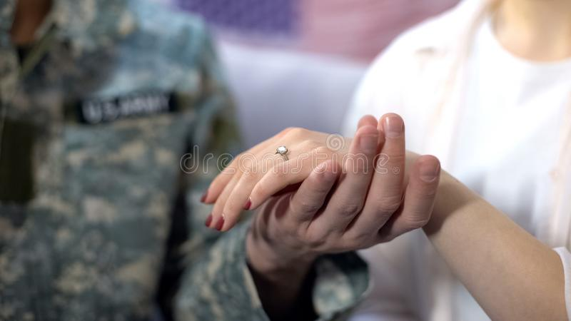 Military officer holding girlfriend hand with engagement ring, proposal close up. Stock photo royalty free stock photos