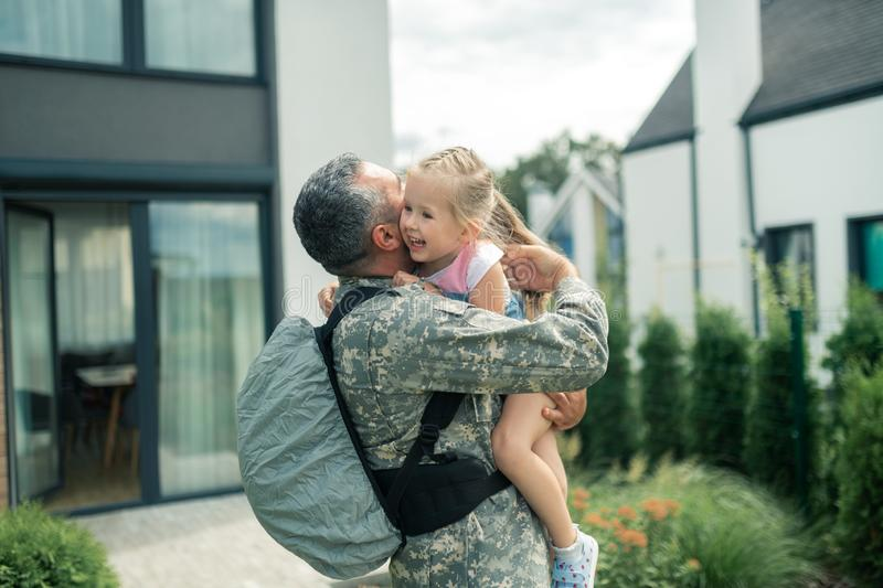 Military officer wearing uniform hugging his tender daughter royalty free stock photo