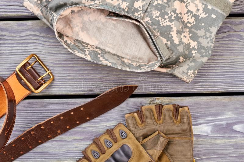 Military outfit, orange belt and fingerless gloves. Wooden desk background stock image