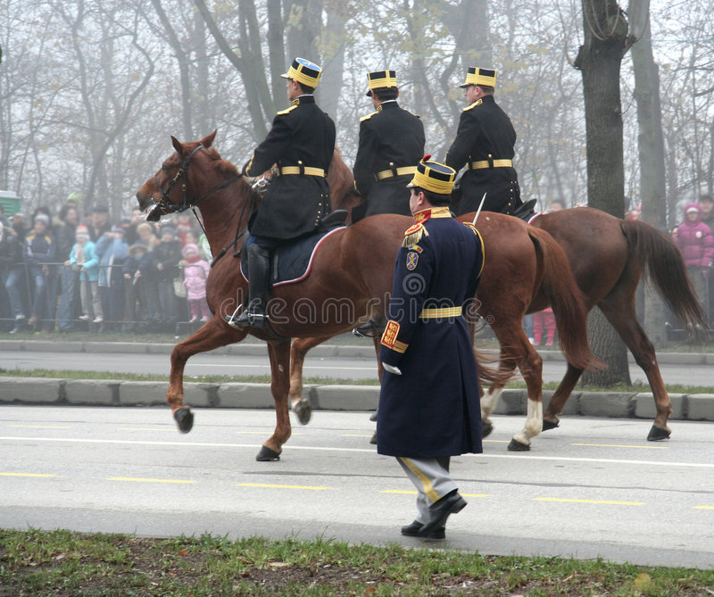 Military parade- horsemen. Three horsemen and one infantry captain marching for the national day royalty free stock image