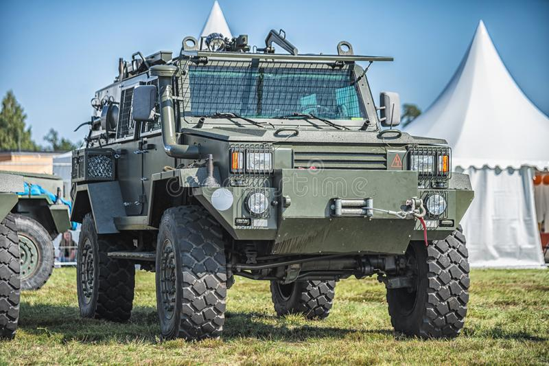 Military patrol car on a green grass. Army war concept. Image of armored vehicle with gun in action. royalty free stock photos