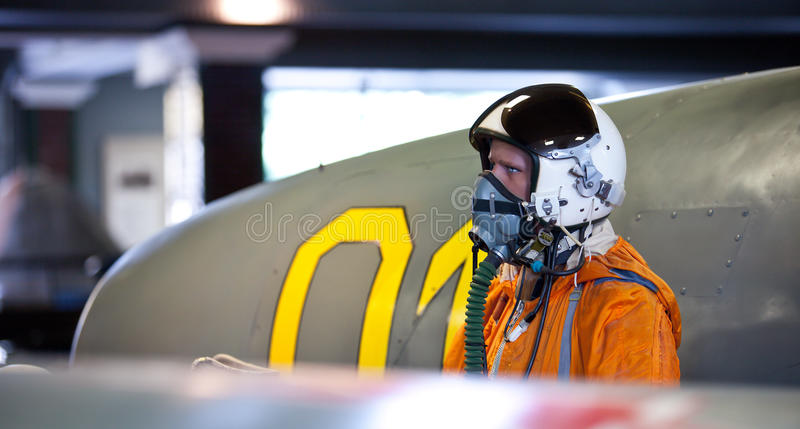 Military Pilot. In the pressurized helmet with oxygen mask near the aircraft royalty free stock photo