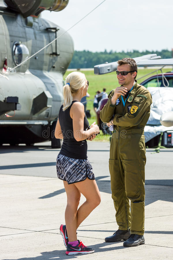 The military pilot and a girl. BERLIN, GERMANY - JUNE 03, 2016: The military pilot and a girl. Exhibition ILA Berlin Air Show 2016 royalty free stock photos