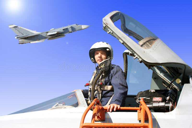 The military pilot in the plane. In a helmet in dark blue overalls against the blue sky royalty free stock photos