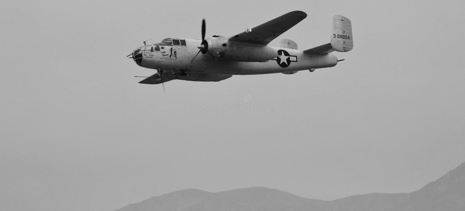 Military Plane. This is a black and white photo of a classic United States military plane in flight with mountains in the background royalty free stock image