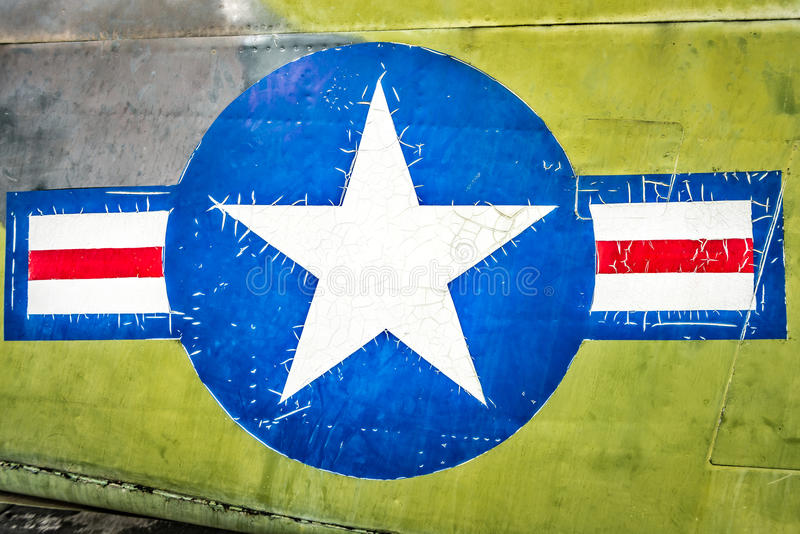 Military plane with star and stripe sign. Part of military airplane with United States Air Force sign. Big white star in blue circle with stripes aside. War stock photography