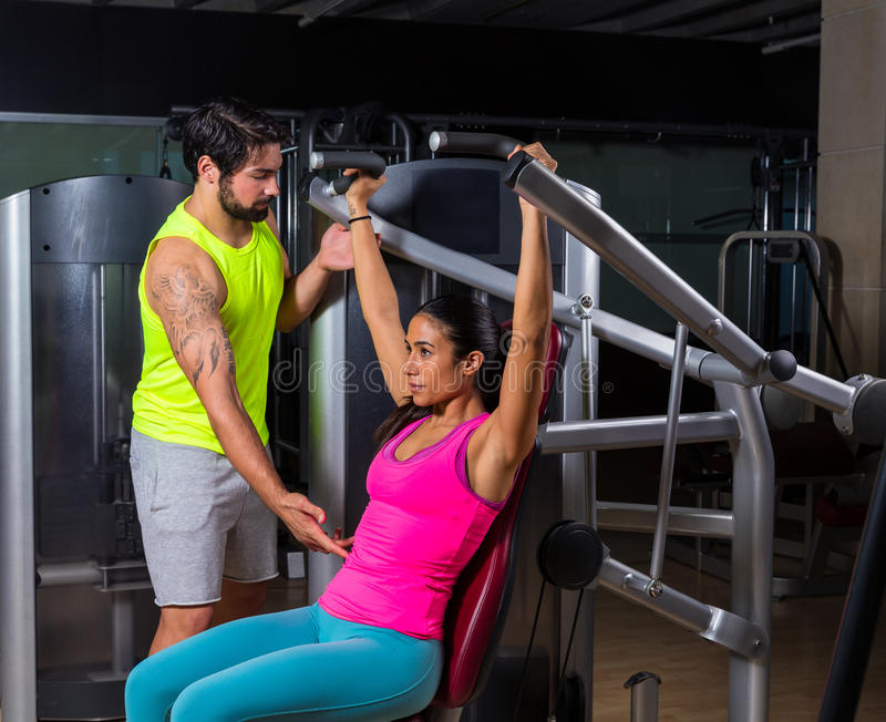 Military press machine woman personal trainer. Military press machine women with personal trainer workout at gym stock image