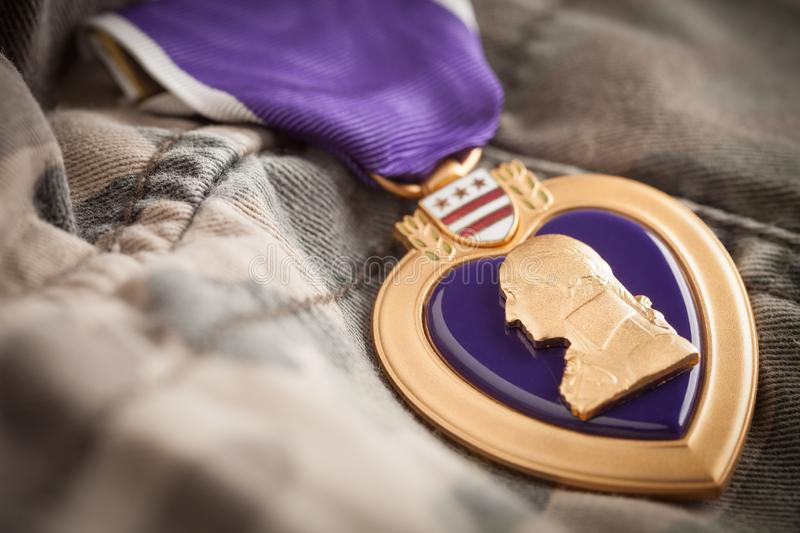 Purple Heart Metal Resting On Camouflage Fatigues. Military Purple Heart Metal Awarded to Soldier Wounded In Combat Resting On Camouflage Fatigues stock photos
